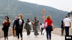 Илустрација - Луѓе со заштитни маски поради Ковид-19 на Камени мост во Скопје