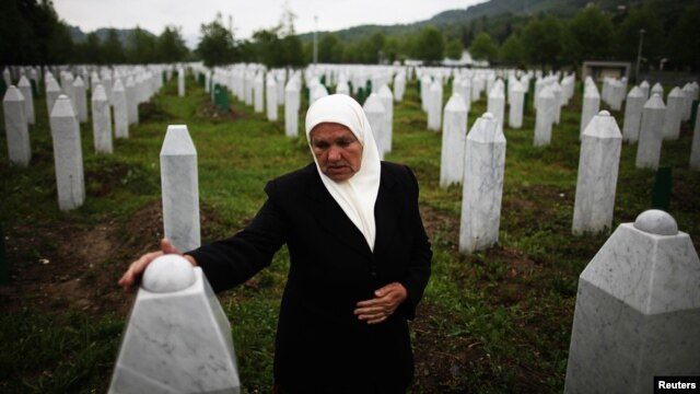 A Bosnian woman stands by the graves of her two sons, who were among some 8,000 men and boys massacred by Bosnian Serb forces in Srebrenica in 1995.