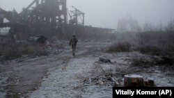 A Ukrainian soldier walks through the fog, past a destroyed coal mine, as he approaches his frontline position in the town of Avdiyivka in the Donetsk region on November 19.