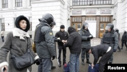 Police officers frisk people near a Moscow train station on December 15, in an effort to ward off more ethnically explosive violence.