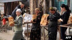 Women haul bread near a street market in Osh, in southern Kyrgyzstan. (file photo)