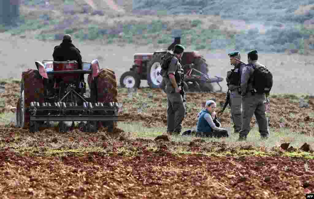 Cisiordania - Soldaţi israelieni discută cu coloniştii evrei din Esh Kodesh, în încercarea de a preveni angajarea palestinienilor la munci agricole, mai la nord de localitatea Jalod. 2 ianuarie 2013 (AFP/JAAFAR ASHTIYEH)
