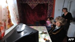 A Kyrgyz family watches a live broadcast of the inauguration of President Kurmanbek Bakiev.