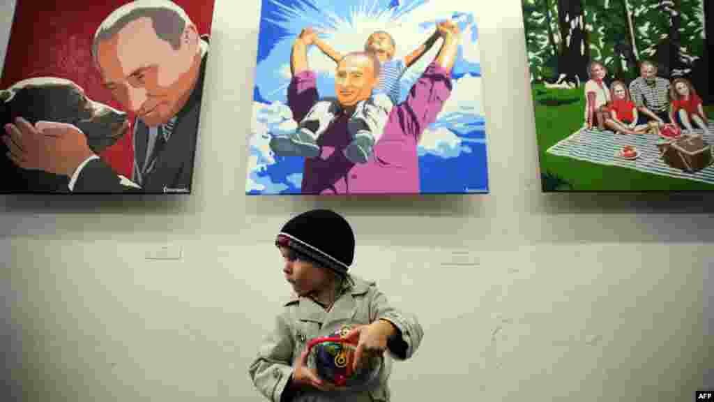 "A boy stands in front of the paintings by artist Aleksei Sergiyenko at his exhibition ""President. The Kindest Person,"" marking the 60th birthday of President Vladimir Putin at the Flacon design workshop in Moscow. (AFP/Andrei Smirnov)"