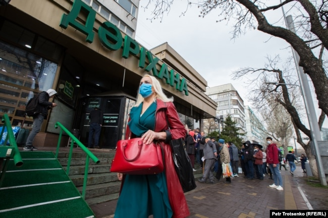 Женщина в маске проходит мимо очереди в аптеку. Алматы, 18 марта 2020 года.