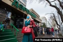 Женщина идет по улице в медицинской маске мимо центральной аптеки. Алматы, 18 марта 2020 года.
