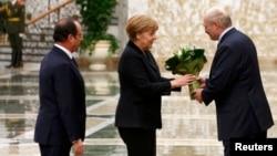 Belarusian President Alyaksandr Lukashenka (right) welcomes German Chancellor Angela Merkel and French President Francois Hollande in Minsk on February 11 for the first day of the Minsk II talks.