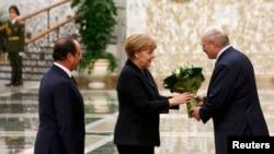 Аляксандар Лукашэнка ўручае кветкі канцлеру Нямеччыны Ангеле Мэркель у Менску 11 лютага 2015 году