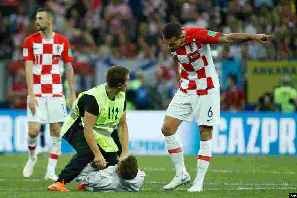 The four stormed the pitch as Croatia was making a drive toward goal.