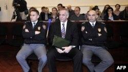 Ivo Sanader məhkəmədə polis əməkdaşlarının arasında oturub. 3 noyabr 2011