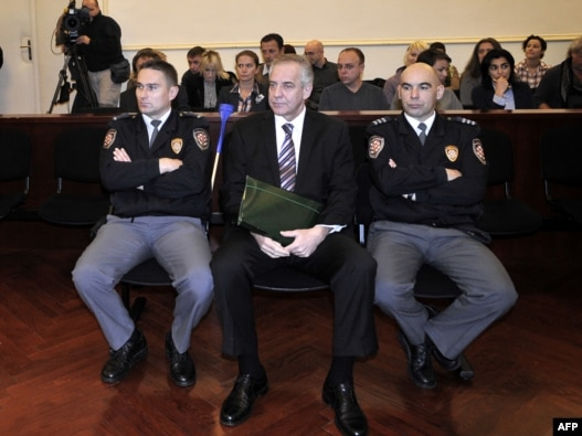 Former Croatian Prime Minister Ivo Sanader is flanked by court policemen at the beginning of his trial in Zagreb on November 3.