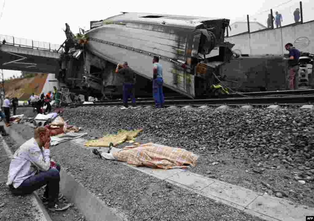 An injured man sits next to the body of one of the some 80 victims killed when a train derailed at high speed on July 24 near the Spanishi city of Santiago de Compostela. (AFP)