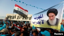 Supporters of the Al Sairun Party, which is backed by the Iraqi Shi'ite cleric Moqtada al-Sadr, hold a poster of Iraq's top Shi'ite cleric, Grand Ayatollah Ali al-Sistani, while attending a campaign rally, ahead of the parliamentary election in Baghdad, Iraq May 4, 2018. FILE