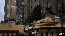 An Egyptian woman stands in front of tanks blocking the street outside the state television building during a demonstration by Coptic Christians in Cairo on March 10.