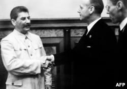 Генеральний секретар секретар ЦК ВКП(б) Йосиф Сталін потискає руку міністру закордонних справ нацистської Німеччини Йоахіму фон Ріббентропу після підписання пакту Молотова-Ріббентропа. Москва, 23 серпня 1939 року