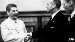 Архіўнае фота. Ёсіф Сталін (зьлева) паціскае руку міністру замежных спраў Нямеччыны Яахіму фон Рыбэнтропу ў Крамлі ў Маскве, 23 жніўня 1939 году