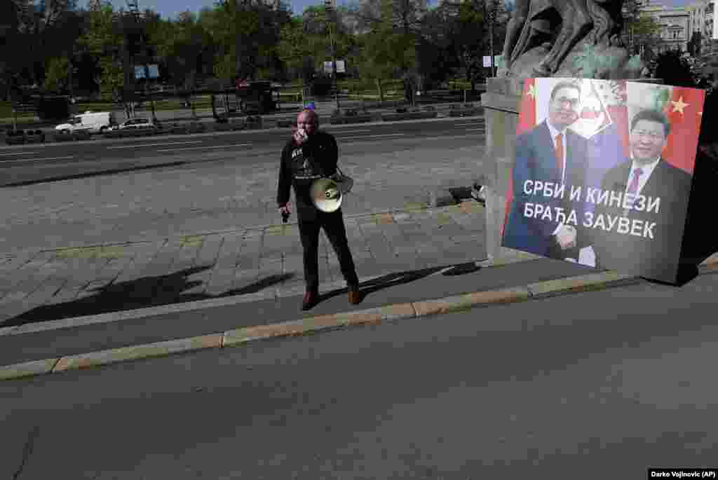 """A protester outside Serbia's National Assembly alongside a sign showing Serbian President Aleksandar Vucic and President Xi that reads, """"Serbs And Chinese, Friends Forever,"""" on April 28.  During a video summit this month, the EU announced a """"robust economic investment"""" for Balkan countries, on top of the 3.3 billion euros ($3.6 billion) in emergency funding the EU had already earmarked for the region. """"The Western Balkans belongs in the EU and there is no question for us about it,"""" European Commission President Ursula von der Leyen said after the summit."""
