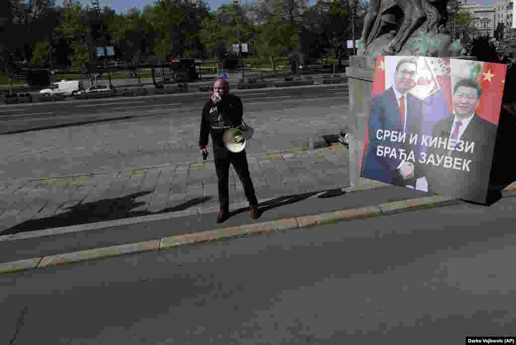 """Un protestatar lângă clădirea Adunării Naționale a Serbiei, alături de un panou cu președintele sârb Aleksandar Vucic și președintele Xi, pe care este afișat mesajul: """"Sârbi și chinezi, prieteni pentru totdeauna"""", în 28 aprilie. În timpul unui summit video din această lună, UE a anunțat o """"investiție economică robustă"""" pentru țările balcanice, de până la 3,3 miliarde de euro (3,6 miliarde de dolari) în fonduri de urgență de la UE deja alocate pentru regiune. """"Balcanii de Vest aparțin UE și nu avem nicio îndoială că ar putea fi altfel"""", a declarat președinta Comisiei Europene, Ursula von der Leyen."""