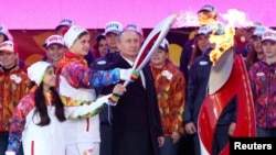 Russian President Vladimir Putin (in suit) was joined by national athletes at a ceremony to mark the start of the Sochi 2014 Winter Olympic torch relay in Moscow on October 6.