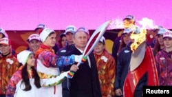 Президент России Владимир Путин (справа) и фигуристы Лина Федорова и Максим Мирошкин зажигают факел на церемонии начала эстафеты олимпийского огня. Москва, 6 октября 2013 года.