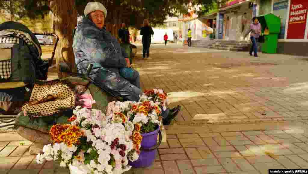 Пенсіонерка торгує хризантемами на вулиці Гайдара