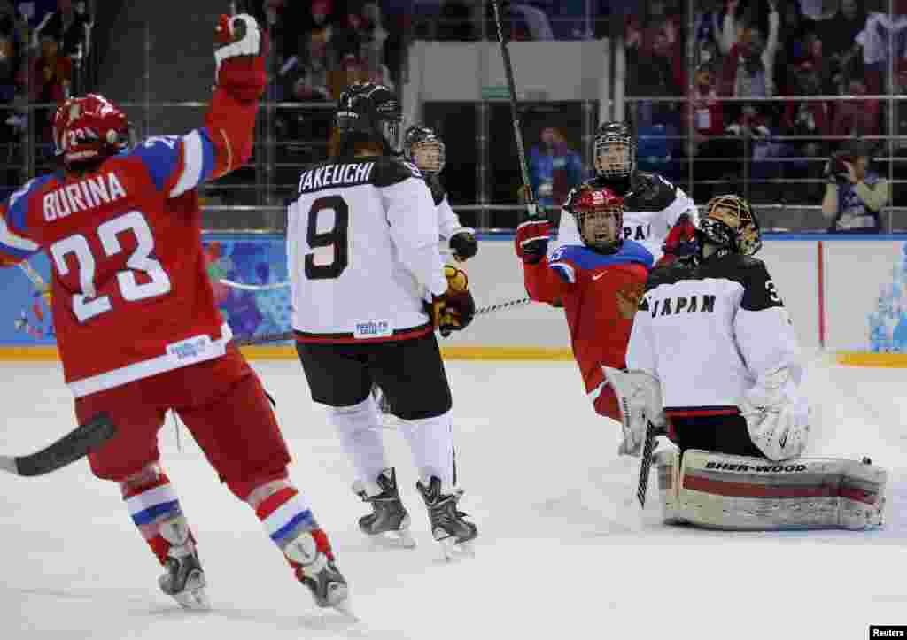 Tatyana Burina (left) of Russia celebrates her goal against Japan during the first period of their women's ice hockey game.