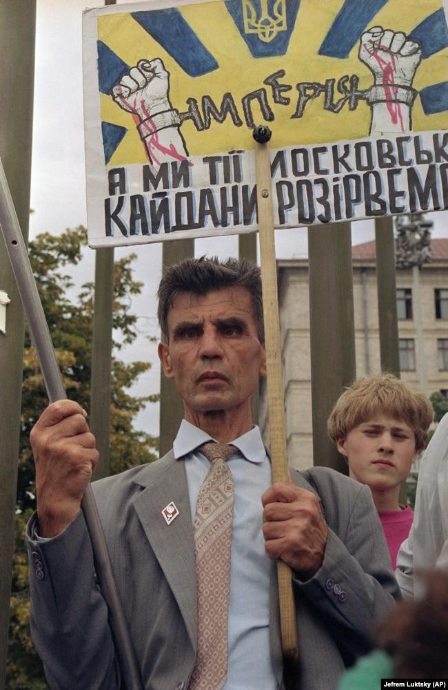 Чоловік тримає транспарант і прапор США в очікуванні на проїзд кортежу американського президента Джорджа Буша, який прибув із візитом до України. Київ, серпень 1991 року