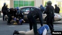 АҚШ полицейлері тәртіпсіздіктер кезінде дүкен тонамақ болған деген күдіктілерді ұстап жатыр. Балтимор, 27 сәуір 2015 жыл.