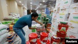 A shop worker arranges the cans of Iranian tomato paste at a super market in the city of Najaf, Iraq October 7, 2018. Picture taken October 7, 2018. REUTERS/Alaa Al-Marjani