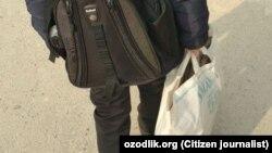 Андижанский школьник несет в школу сумку с дровами для обогрева класса.