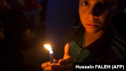 نوجوان عراقی بهیاد قربانیان شمع روشن کردهاست؛ ۲۱ آبان، بصره