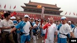 Хейн Вербругген, председатель координационной комиссии МОК, несет Олимпийский факел во время эстафеты огня у ворот Тяньаньмэнь в Пекине, 6 августа 2008