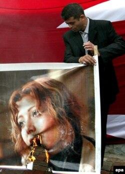 Türkiyədə Elif Şafaka etiraz edən şəxs onun məhkəməsi gedən binanın qarşısında posterini yandırır.