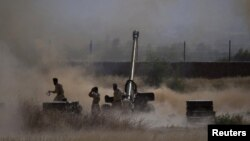 Army soldiers are silhouetted by artillery smoke while firing towards militant targets in Mohmand district (file photo).