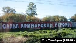 """Надпись """"Слава приморским героям"""" на заборе вдоль железной дороги в ближнем Подмосковье"""