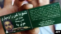 A Pakistasni man holds a matchbox cover in July 2006 announcing a reward for information leading to the capture of suspected senior Al-Qaeda leader Adnan El Shukrijumah.