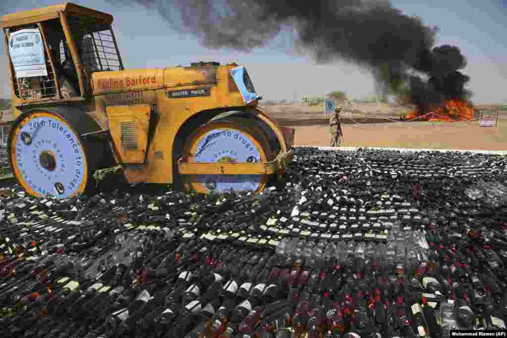 Pakistani authorities smash confiscated bottles of alcohol and burn drugs in Karachi. (AP/Muhammad Rizwan)