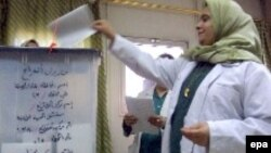Iraq -- An Iraqi nurse casts her ballot in a box in an election station at a local hospital in Baghdad on Monday 12 Dec. 2005
