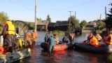 RUSSIA -- Members of the Russian Emergencies Ministry evacuate people during a rescue operation in a flood-affected town of Tulun in Irkutsk Region, Russia July 1, 2019.