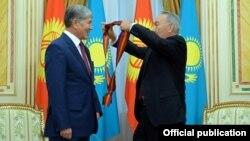 Президент Казахстана Нурсултан Назарбаев вручает орден президенту Кыргызстана Алмазбеку Атамбаеву. Астана, 7 ноября 2014 года.
