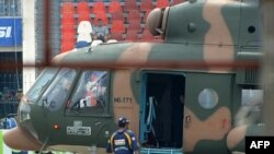 A Sri Lankan cricketer boards a Pakistani military helicopter to evacuate from Gaddafi Stadium in the wake of the deadly attack on March 3.