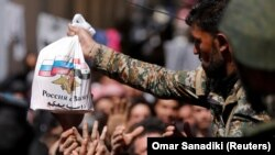 Сирийский военный раздает пакеты с помощью от России жителям, покинувшим Восточную Гуту и доставленным в лагерь близ Дамаска. 20 марта 2018 года.
