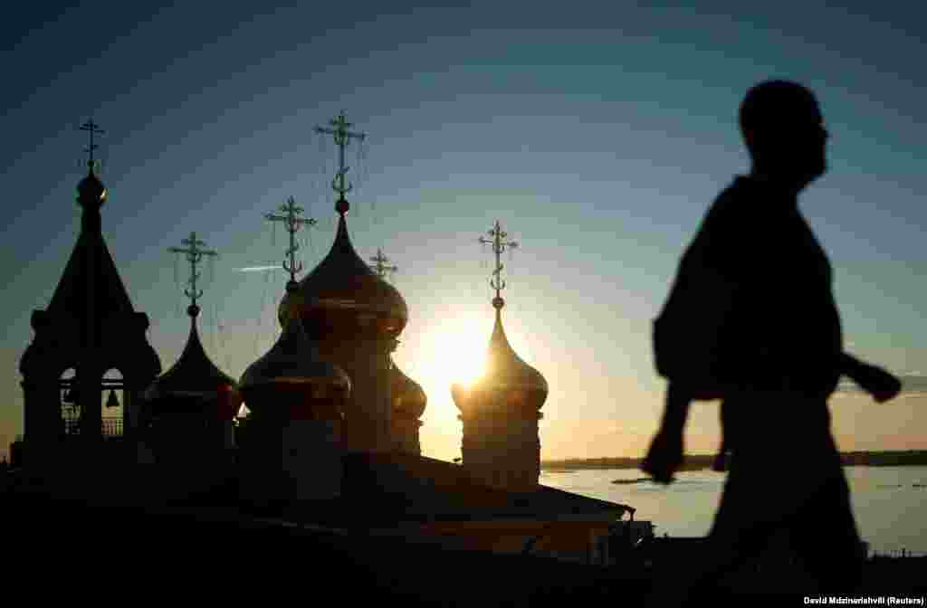 A man passes a church during sunset in Nizhny Novgorod, Russia, on July 11. (Reuters/David Mdzinarishvali)