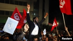 Ennahda supporters celebrate outside the group's headquarters in Tunis on October 25.