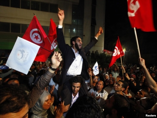 Supporters of the Islamist Ennahda movement celebrate outside the group's headquarters in Tunis on October 25.