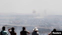 Ізраїльтяни і туристи спостерігають за боєм у Сирії з ізраїльського боку лінії перемир'я на Голанських висотах, 7 червня 2013 року