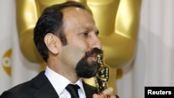 "Asghar Farhadi, director of Iranian film ""A Separation,"" kisses his award for best foreign-language film."