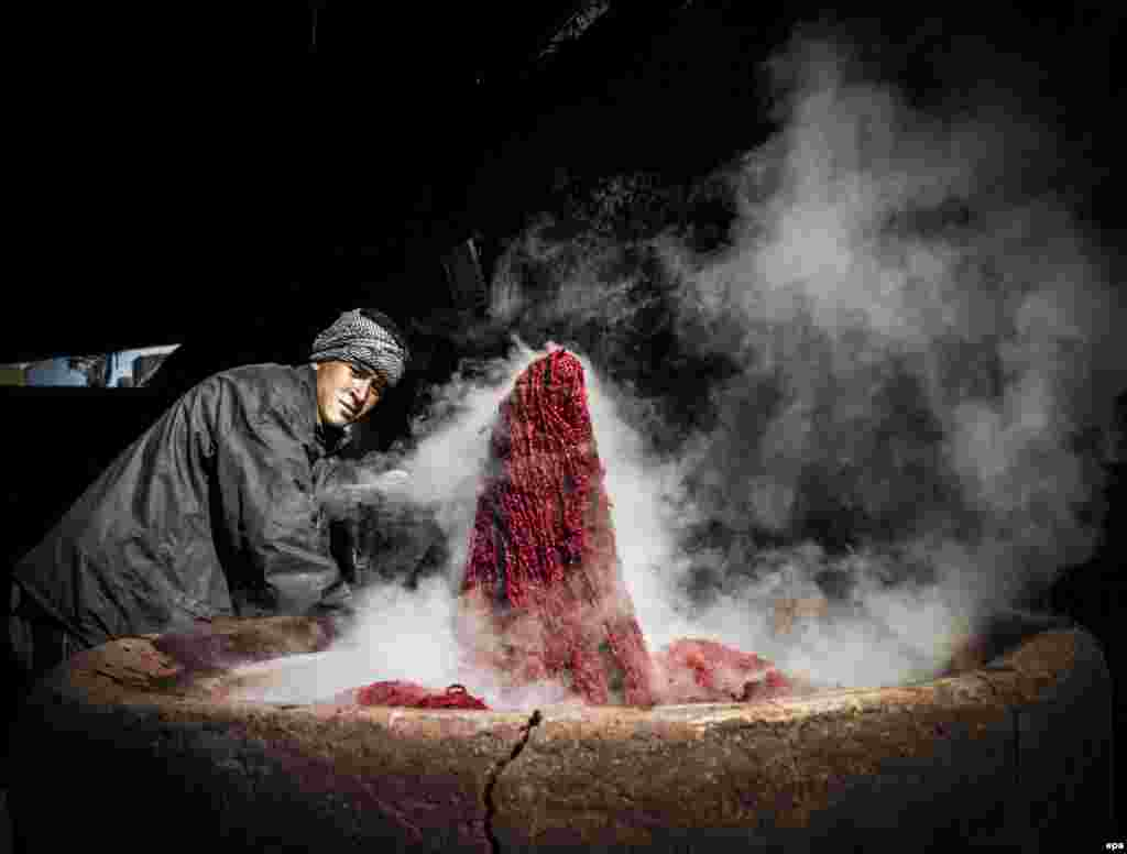 A man dyes threads to be used in weaving carpets at a factory in Kabul. (epa/Hedayatullah Amid)