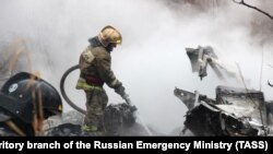 A firefighter works at the site of a helicopter crash in Khabarovsk on April 11.