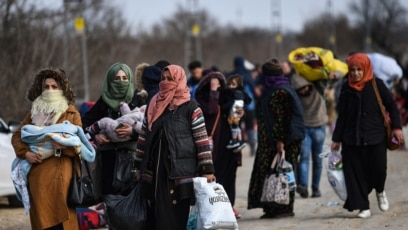 Migrants carry their belongings in Edirne on March 4, 2020